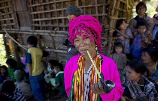 An ethnic Chin woman of the Muun sub-tribe with traditional tattooed face smokes a pipe in Kyar Do village. (AP Photo/Gemunu Amarasinghe)