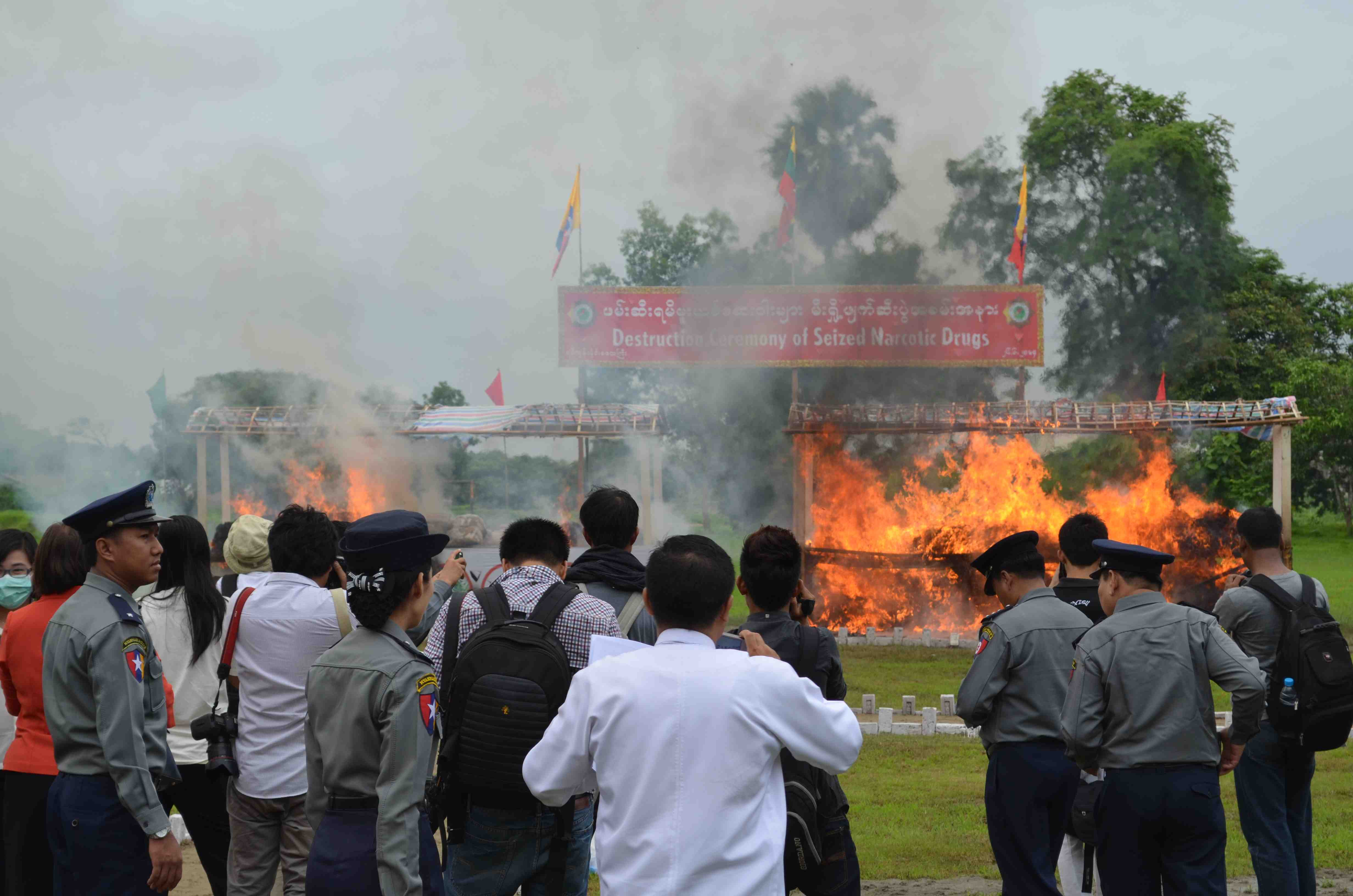 Police and media look on as an estimated US$ 14 million dollars worth of seized drugs burn at an event in Rangoon's Hlawga township on June 26. (PHOTO: Alex Bookbinder)