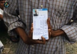 A striking Burmese migrant displays his punch-card.