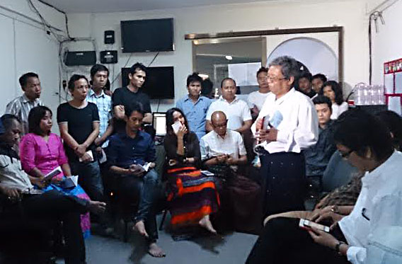 Thiha Saw (standing, right) speaks to DVB staff about a new code of ethics introduced by the interim Press Council in August 2014. (Photo: DVB)