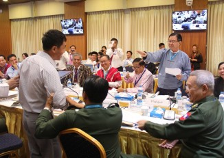 "During ceasefire talks in Rangoon on Saturday between the ethnic alliance NCCT and the Burmese government's UPWC, Minister Aung Min went over to NCCT side to discuss a point with ethnic delegates. Someone from the government side shouted cheerfully, ""You are on the wrong side!"" at which point the KIO's Gen. Gun Maw moved to take up a seat alongside the UPWC, declaring, ""I am on this side now"". The exchange provoked much laughter, followed by a round of applause. (PHOTO: Myanmar Peace Centre)"