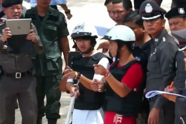 Burmese suspects Zaw Lin and Win Zaw are made to reenact the crime on the island of Koh Tao. (Screenshot: Reuters)