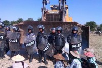 Riot police prepare to clear villagers out of the path of a bulldozer at Latpadaung copper mine site in Sagaing Division on 23 December 2014. (PHOTO: Han Win Aung)