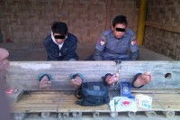 Policeman Thein Htay Aung, right,  and Sai Tun Hseng are held in stocks after being apprehended for drug possession in northern Shan State on 23 January (Photo: DVB)