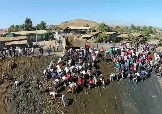 Scavengers sort through a pile of soil unearthed by industrial jade mining companies. (Photo: DVB)