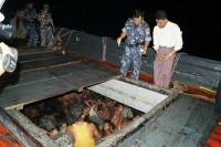 Burmese naval officers check the hull of a ship intercepted off the coast of Arakan State on 21 May 2015.  Two hundred and eight souls were discovered.(PHOTO: Ministry of Information)