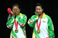 Aye Thit Sar Myint (left) and Myat Thet Su Wai Phyo cry as they receive their gold medals for winning the women's dual event in wushu.