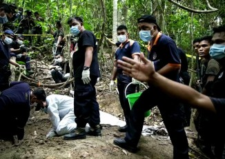 Malaysian officials investigate a mass grave in the Bukit Wang Burma forest, Wang Kelian, Perlis, near the Malaysia-Thailand border. (PHOTO: Reuters)