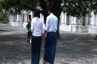 A young Burmese couple hold hands out the front of a pagoda. (PHOTO: DVB).