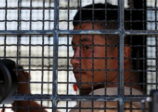 File photo: Burmese migrant worker Win Zaw Htun sits in a prison truck as he arrives at Koh Samui Provincial Court. (PHOTO: Reuters)