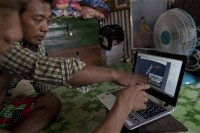 In this 1 July photo, former Burmese slave fishermen Kaung Htet Wai, left, and Lin Lin, second left, point to a satellite image of a refrigerated cargo ship owned by Silver Sea Fishery Co in waters off Papua New Guinea, while looking at a laptop screen in their home in Rangoon. (PHOTO: AP)