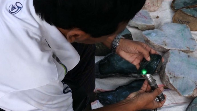 A potential buyer examines a piece of jade at Naypyidaw's gem emporium. (PHOTO: DVB).