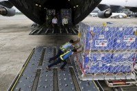 Workers unload aid from an Royal Australian Air Force transport plane carrying donated aid for Burma's flood victims at Yangon International Airport on 10 August 2015. (PHOTO: REUTERS)