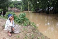 A villager in Monywa District looks on as floodwaters consume his neighbourhood. (PHOTO: DVB)