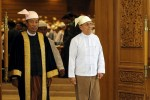 Shwe Man (left), Speaker of the Union Parliament, and Burma's President Thein Sein exit parliament on 26 March 2014. (PHOTO: Reuters)