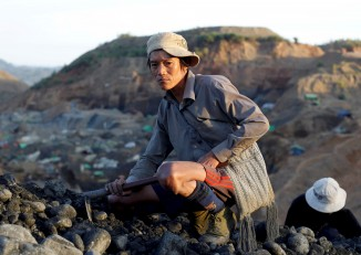 A miner takes a rest while searching for jade stones at a mine in Hpakant, Kachin State, in November 2015. (Photo: Soe Zeya Tun / Reuters)