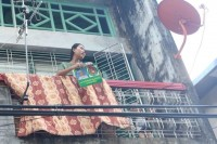 A woman on a balcony in an apartment block in Thinganggyun Township, Rangoon, with USDP campaign material bearing the president's image, on 3 November (PHOTO: Myanmar Now/Phyo Thiha Cho