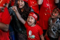 Supporters, young and old, celebrate as they watch official results from the Union Election Commission on an LED screen in front of the National League for Democracy Party (NLD) head office in Rangoon, 9 November 2015. (PHOTO: Reuters)