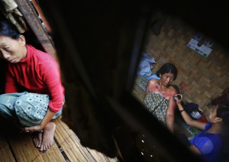 Yaw Myaw (R) applies a traditional healing method for fever using a sharp tin can on her mother Zawn Lum. PHOTO: Reuters