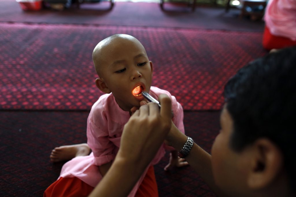 A doctor examines a Buddhist novice nun in the Healthy Farm charity clinic at a monastery outside Rangoon November 2, 2013. PHOTO: Reuters