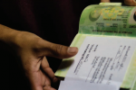 A woman who works at a hotel on the Thai resort island of Phuket shows her work permit in her passport. (Photo: Schyst Resande / Fair Action)