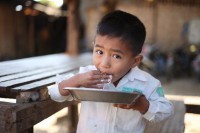 A five-year-old IDP child enjoys his lunch - mainly rice with some oil - after school at the Zi Un displacement camp in Myitkyina on 7 January 2016. (PHOTO:Thin Lei Win/Myanmar Now)