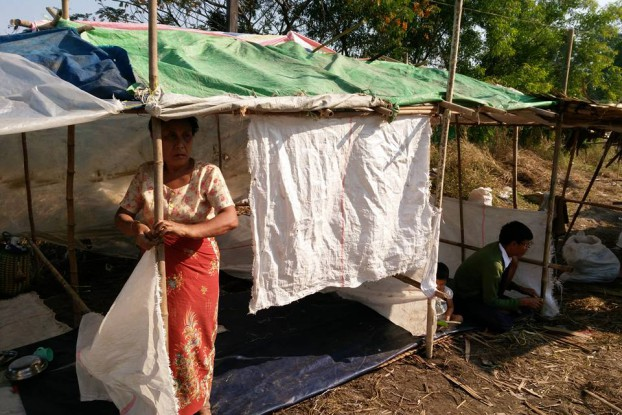 A former resident of land reclaimed by the Burmese army stands in her makeshift home near Rangoon. (PHOTO:DVB)