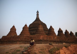 A local man reads a booklet in front of a Mrauk-U pagoda. (Photo: Thin Lei Win / Myanmar Now)