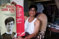"""Robert Sann Aung posing with a poster of himself. """"These awards are my shield; being well known protects me."""" (Photo: Bill O'Toole / DVB)"""
