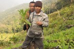 A villager in Chin State hold up a juvenile poppy plant. (Photo: Free Burma Rangers)