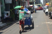 A man pushes a cart loaded with water bottles on a street in Rangoon. (Photo: Htet Khaung Linn / Myanmar Now)