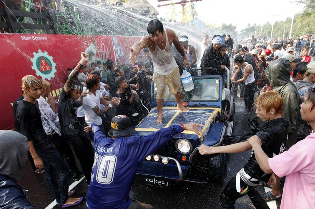 Locals ride in vehicles get sprayed with water while celebrating Thingyan, Burma's New Year water festival. (Reuters)
