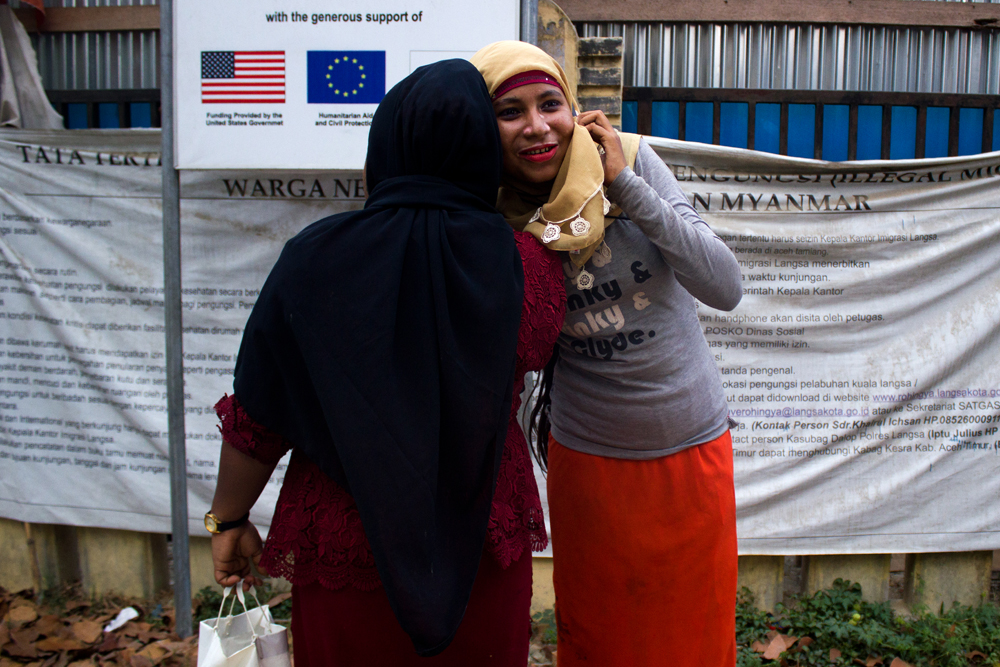 Two Rohingya women speak on the phone with their relatives in Burma at the entrance of Lhok Bani Refugee Camp, in Langsa City (Aceh Province, Indonesia). Photo: Carlos Sardiña Galache / Yayasan Geutanyoe – A Foundation for Aceh.