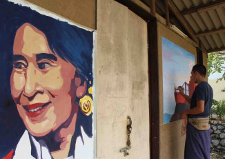 An artist paints a mural on one of the buildings that will be part of the Mae Tao Clinic at its new location in Mae Sot, Thailand. (Photo: Libby Hogan / DVB)