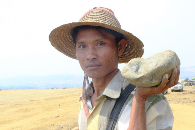 Maung Aye, a miner who has worked in Hpakant for many years, holds a piece of low-grade jade. (Htet Khaung Linn / Myanmar Now)