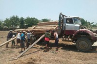 A truck being loaded with timber confiscated from illegal loggers. Officials were later forced by men with swords and clubs to return the stolen timber. (Photo: DVB)