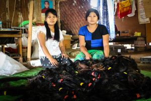Two women sit before a pile of donated hair for the bridge- and road-building project in Sagaing Division. (Photo: Libby Hogan / DVB)