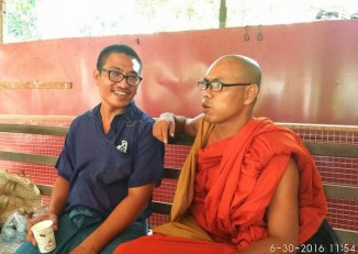 Nyi Nyi Lwin sits with a monk as he awaits a hearing outside Thanlyin township court on 30 June 2016. (PHOTO: DVB)