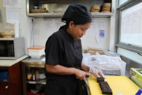 A trainee cuts brownies at the Yangon Bakehouse, where women from disadvantaged backgrounds learn skills that will help them find work or start their own businesses. (Photo: Libby Hogan / DVB)