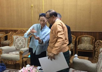 UNDP  Ambassador for Road Safety Michelle Yeoh shows photographs to Burma's Transportation and Communications Minister Thant Zin Maung in Naypyidaw on 15 June 2016.