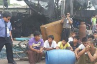 Some of the rescued workers appear with Thai anti-human-trafficking officials. (Photo: MAT / Facebook)