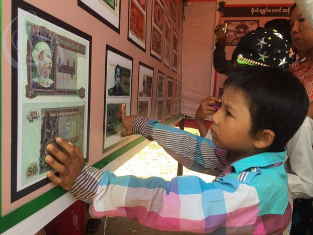 A boy looks at Burmese banknotes bearing portraits of Aung San at a museum honouring Burma's independence hero in his hometown of Natmauk, Magway Division, on 19 July 2016. (Photo: DVB)