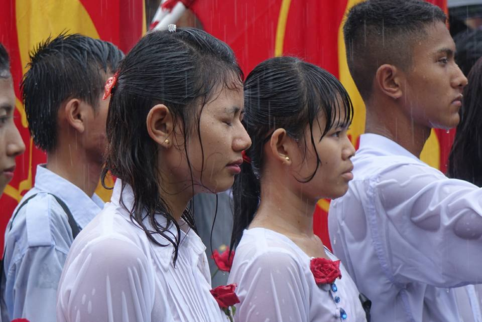 Students stand in the rain in Rangoon at an event to mark Martyrs' Day on 19 June 2016.