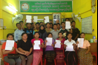 Burmese migrant workers from a poultry farm in Thailand's Lopburi Province hold up application forms for compensation after accusing their former employer of forcing them to work under slave-like conditions. (Photo: MWRN)