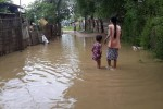 A mother and daughter wade through a flooded street in Prome, Pegu Division. (PHOTO: DVB)