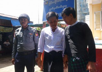 Hla Phone, center, appears outside a court with his lawyer on 22 August 2016. (Photo: DVB)