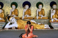 A Burmese woman prays in front of images of Buddha at Shwedagon Pagoda. (Photo: Reuters)
