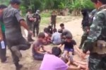 A screen capture from a video circulating on the Internet shows a man in KNU uniform about to kicked a handcuffed youth.