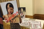 A woman holds up a poster showing the face of an acid-attack victim. (Photo: Aye Lae / DVB)