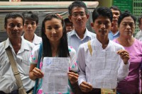 Residents of a squatter community in Rangoon's Hlegu Township hold up an eviction letter telling them to leave the area by early September 2016. (Photo: Libby Hogan / DVB)